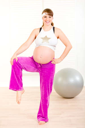 Smiling beautiful pregnant woman doing exercise at living room Stock Photo - 8431744