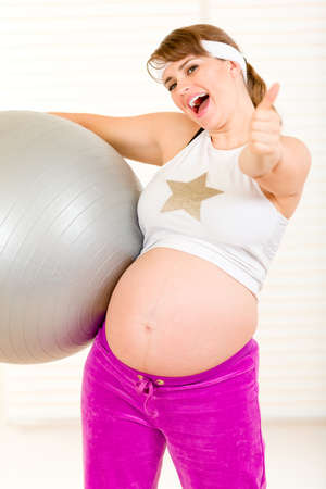 Smiling  pregnant woman holding fitness ball and showing thumbs up gesture  photo
