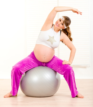 Smiling beautiful pregnant woman doing exercises on  fitness ball at living room