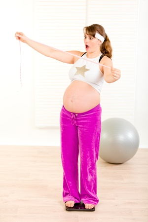 Shocked pregnant woman standing on weight scale and holding  measure tape in hand
