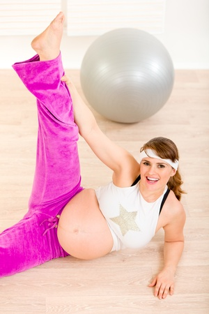 Smiling beautiful pregnant woman doing fitness exercises at living room  photo
