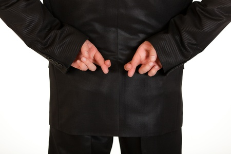 crossed fingers: Businessman holding crossed fingers behind back isolated on white.  Close-up.  Stock Photo