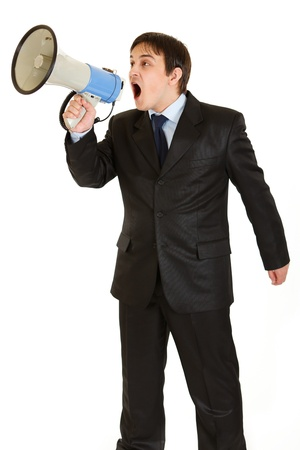 Frustrated young businessman yelling through megaphone isolated on white  photo