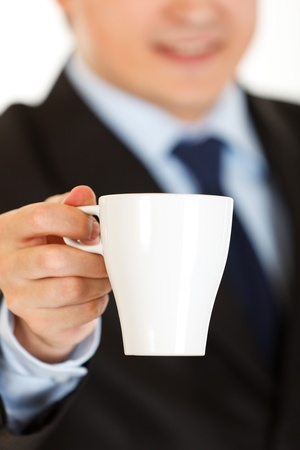 Smiling businessman offering cup of coffee. Closeup.  photo
