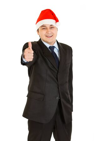 Happy young businessman in Christmas hat showing  thumb up gesture isolated on white   photo