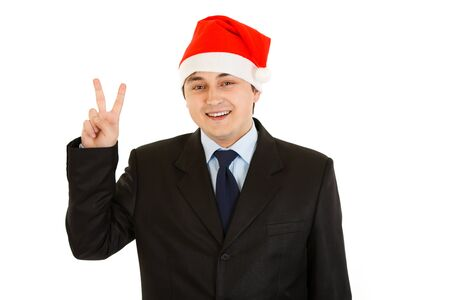 Happy young businessman in Santa hat showing victory gesture isolated on white .   photo