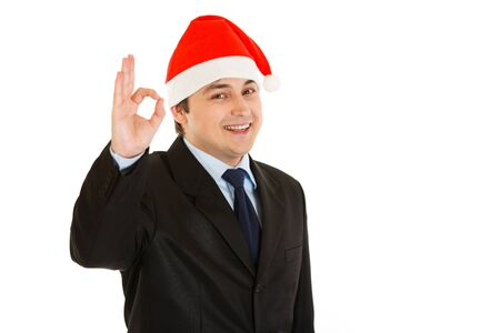 Happy young businessman in Christmas hat showing ok gesture isolated on white .  photo