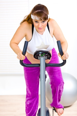 static bike: Smiling pregnant woman working out on static bike at home  Stock Photo