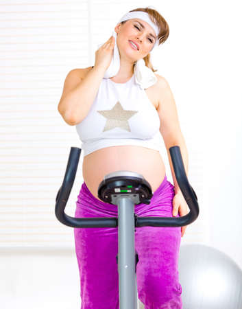 static bike: Beautiful pregnant woman wiping her face with towel after training on static bicycle