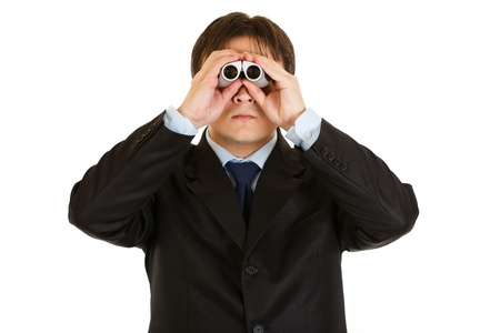 Serious young businessman looking through binoculars isolated on white  photo
