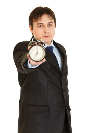 certitude: Serious young businessman holding alarm clock in hand isolated on white