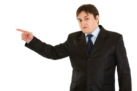 pointing finger: Shocked young businessman pointing  finger in corner  isolated on white