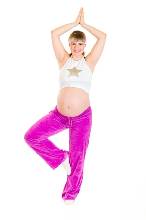Smiling beautiful pregnant woman doing yoga isolated on white  photo