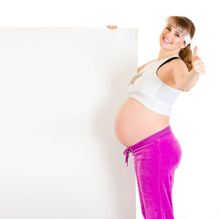 Smiling beautiful pregnant woman holding blank billboard and showing thumbs up gesture isolated on white  photo
