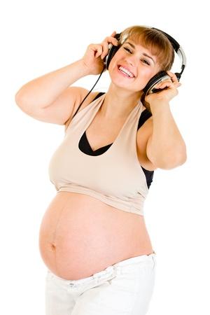 listening to music: Mujer embarazada feliz de escuchar m�sica en auriculares aislados en blanco  Foto de archivo