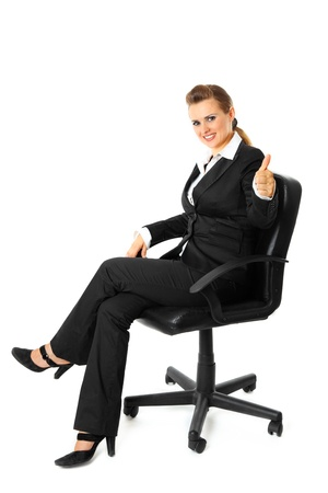 Smiling modern business woman sitting on chair and showing thumbs up gesture  isolated on white  photo