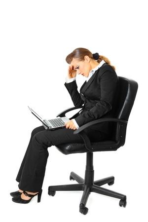 cansancio: Mujer de negocios modernos de cansancio sentado en silla y usa port�til aislado en blanco