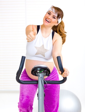 static bike: Smiling pregnant woman sitting on static bicycle and showing thumbs up gesture  Stock Photo