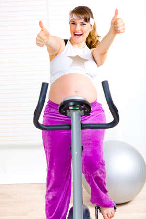 static bike: Happy pregnant woman sitting on static bicycle and showing thumbs up gesture