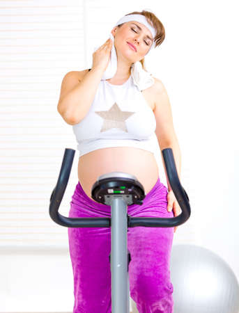 static bike: Beautiful pregnant female wiping her face with towel after training on static bicycle