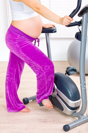 Pregnant female preparing for workout on stationary bicycle. Closeup.