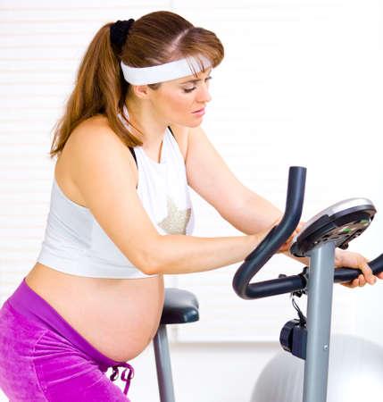 belle femme enceinte: Belle femme enceinte se pr�parer pour entra�nement sur v�lo stationnaire  Banque d'images