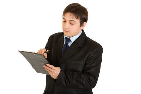 making notes: Serious young businessman making notes in document isolated on white  Stock Photo