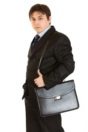 certitude: Serious young businessman holding briefcase on shoulder isolated on white