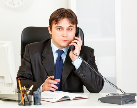 certitude: Thoughtful modern business man talking on phone and making notes in diary