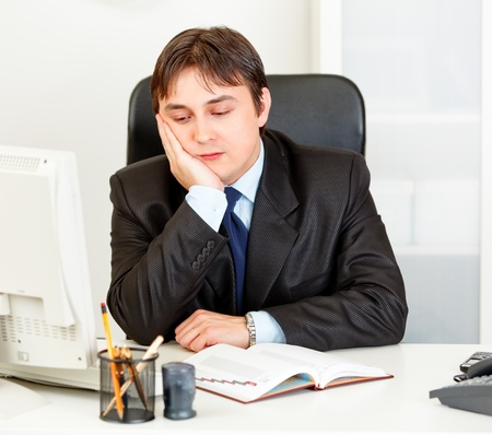 Bored modern business man sitting at desk in  office  photo