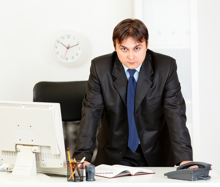 Strict modern business man standing at office desk Stock Photo - 8624542