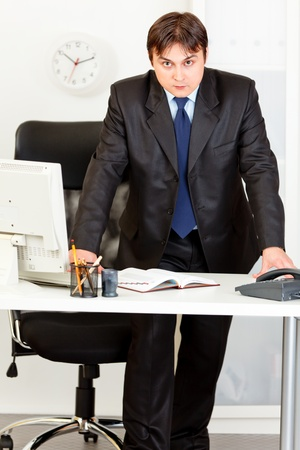 Strict modern business man standing at office desk Stock Photo - 8624572