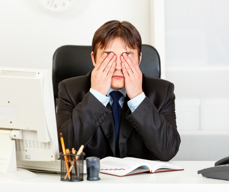 Modern business man sitting at office desk and making see no evil gesture  photo
