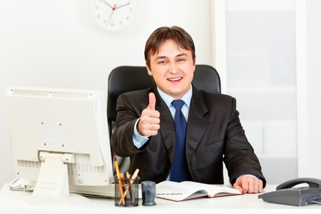 Smiling modern business man sitting at office desk and showing thumbs up gesture