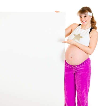 Smiling beautiful pregnant woman pointing on blank billboard isolated on white  photo