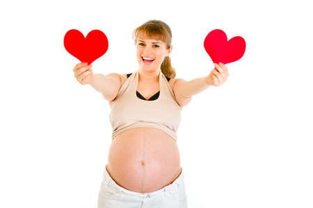 unison: Happy pregnant woman holding two paper hearts in hands isolated on white. Concept - two hearts beating in unison.
