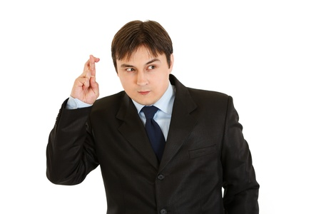crossed fingers: Superstitious young businessman holding crossed fingers isolated on white