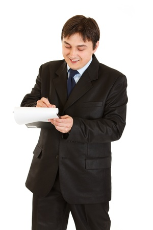 Smiling young businessman making notes in document isolated on white  photo
