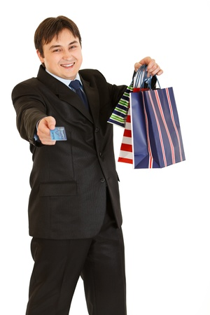Smiling young businessman with shopping bags giving credit card isolated on white  photo
