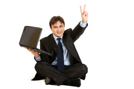 Sitting on  floor with laptop smiling businessman showing victory gesture isolated on white  photo