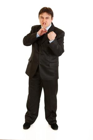 empresario enojado: Hombre de negocios enojado con el dedo en la boca y amenazan con pu�o aislado en blanco