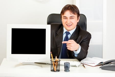 Smiling  businessman sitting at office desk and pointing finger at blank screen  monitor   photo