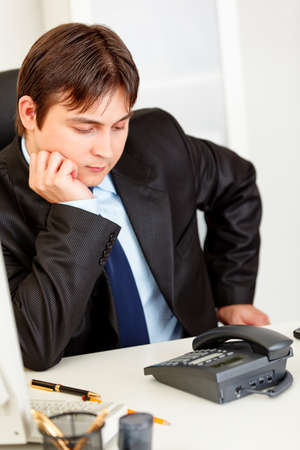Concentrated business man sitting at office desk and expecting phone call Stock Photo - 8841216