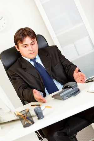 displeased: Displeased business man sitting at office desk and waiting important phone call