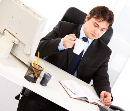 centrality: Concentrated business man with cup of tea sitting at office desk and checking timetable in diary  Stock Photo
