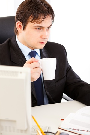 Thoughtful businessman  sitting at office desk  and holding cup of tea in hand  photo