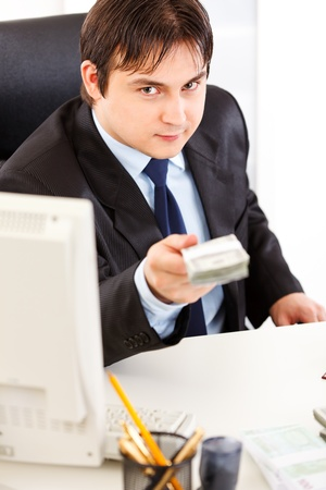 Smiling  business man sitting at office desk and giving dollars packs  photo