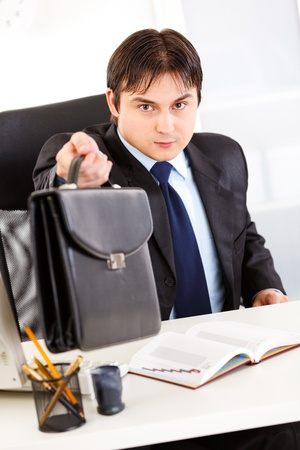 Attentive business man sitting at office desk and giving briefcase  photo