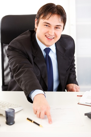 Smiling  business man sitting at office desk and pointing on document for signature  photo