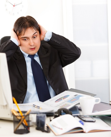 Shocked young business man sitting at office desk overloaded with work   photo